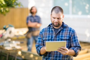 Manual Worker Using Digital Tablet With Coworker Standing In Bac